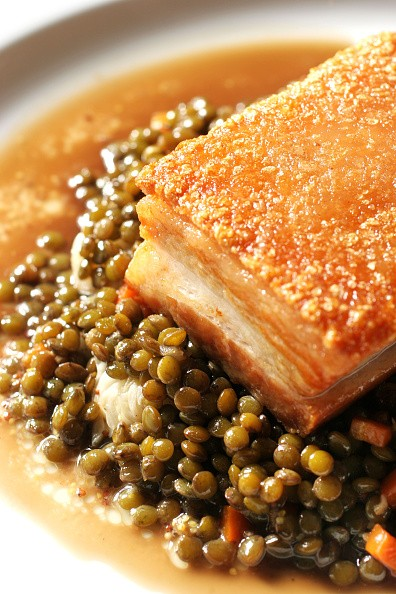 Dish of Bangalow Pork Belly with stock-braised lentils and mustard cabbage