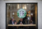 Patrons sit in a Starbucks Coffee shop in central London