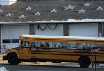A school bus returning with children from the new Sandy Hook School passes the fire station with stars on the roof to honor those killed in the shooting, in Sandy Hook