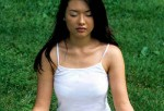 A woman doing meditation outdoors.