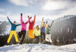 Six friends jumping in snow