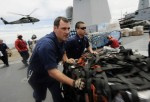 In this handout image provided by U.S. Navy, Sailors aboard the U.S. 7th Fleet command ship USS Blue Ridge (LCC 19) move pallets of humanitarian relief supplies across the ship's flight deck