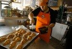 Bernice Ornelas, a manager and cook at La Monarca Bakery, adds topping to chocolate croissants