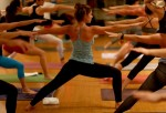 Amy Steiner (C) leads a yoga class while dressed in Lululemon Athletica yoga clothes at the Green Monkey yoga studio