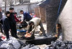 Health department administration officers destroy reclaimed New Orleans roast chicken wings, chicken hamburgers and sauces from Kentucky Fried Chicken (KFC), contaminated by the cancer-causing food dye Sudan I March 18, 2005 in Xian of Shaanxi Province, C