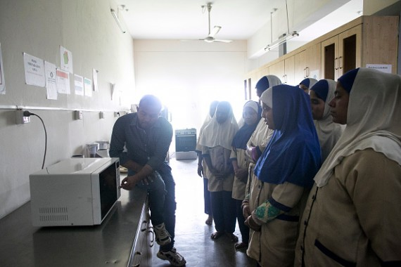 Women are instructed on using the microwave at the Sheikh Fazilatunnesa Mujib Mohila Technical Training Center on March 14, 2016 in Dhaka, Bangladesh.