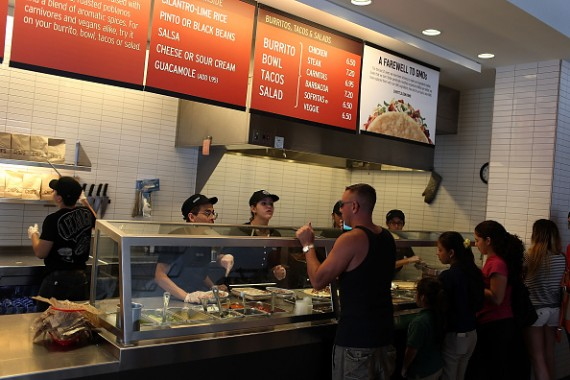 Chipotle restaurant workers fill orders for customers on the day that the company announced it will only use non-GMO ingredients in its food on April 27, 2015 in Miami, Florida.