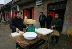 A Chinese farmer (R) buys tofu, a healthy meat substitute, from a family factory for the upcoming Chinese Lunar New Year Feb. 6, 2005 in the countryside of Jinzhai County, Anhui Province, China.