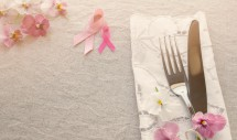 Pink ribbon table setting with pink flowers, copy space toning background